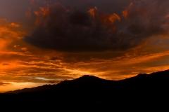 Abendrot mit dunkler Wolke über Bergkette